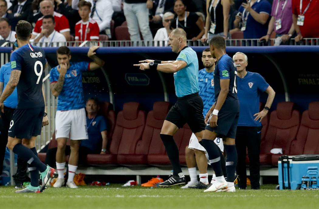 Referee Nestor Pitana from Argentina points to the penalty box after watching the VAR monitor, during the final match between France and Croatia at the 2018 soccer World Cup in the Luzhniki Stadiu ...