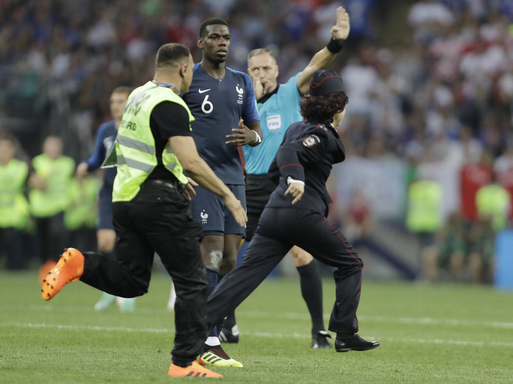 France's Paul Pogba watches a security staffer chasing a pitch invader during the final match between France and Croatia at the 2018 soccer World Cup in the Luzhniki Stadium in Moscow, Russia, Sun ...