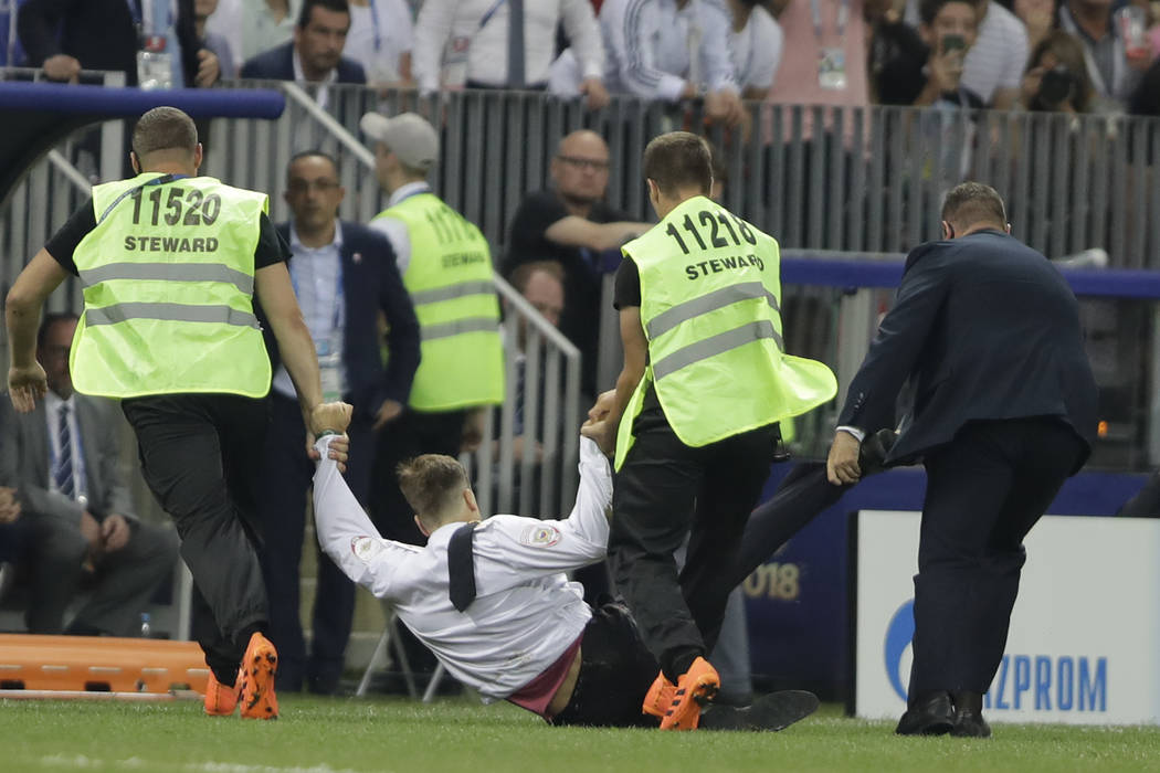 Security personnel drag a fan that jump onto the pitch during the final match between France and Croatia at the 2018 soccer World Cup in the Luzhniki Stadium in Moscow, Russia, Sunday, July 15, 20 ...