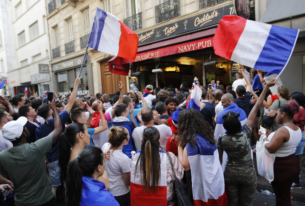 French soccer team supporters wave French flags as they watch the soccer World Cup final match between France and Croatia, Sunday, July 15, 2018 in a cafe in Paris. (AP Photo/Francois Mori)