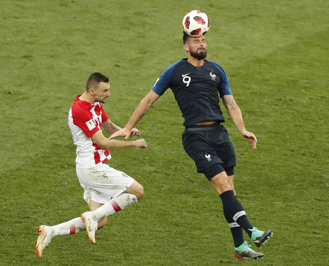 Croatia's Mario Mandzukic, left, and France's Olivier Giroud challenge for the ball during the final match between France and Croatia at the 2018 soccer World Cup in the Luzhniki Stadium in Moscow ...