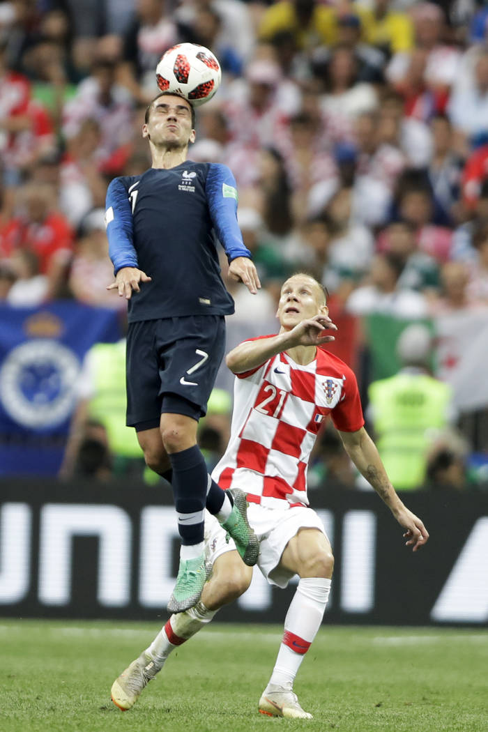 France's Antoine Griezmann heads the ball under the watch of Croatia's Domagoj Vida during the final match between France and Croatia at the 2018 soccer World Cup in the Luzhniki Stadium in Moscow ...