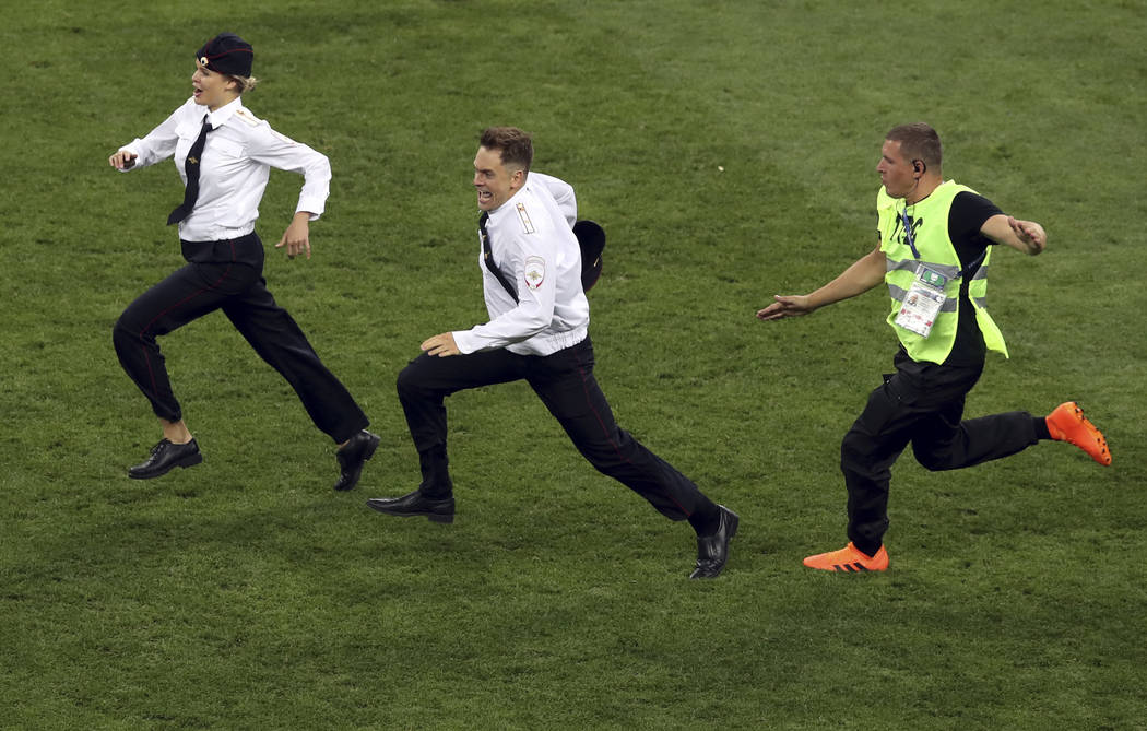 A steward runs after two people that invaded the pitch during the final match between France and Croatia at the 2018 soccer World Cup in the Luzhniki Stadium in Moscow, Russia, Sunday, July 15, 20 ...