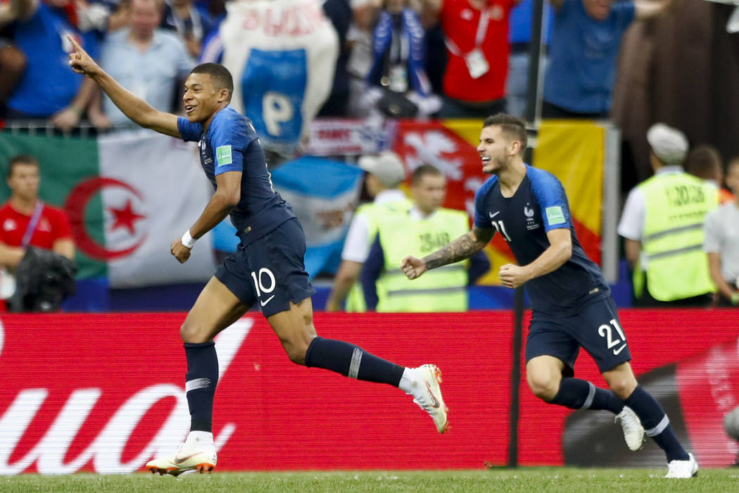 France's Kylian Mbappe, left, celebrates after scoring his side's fourth goal with France's Lucas Hernandez, right, during the final match between France and Croatia at the 2018 soccer World Cup i ...