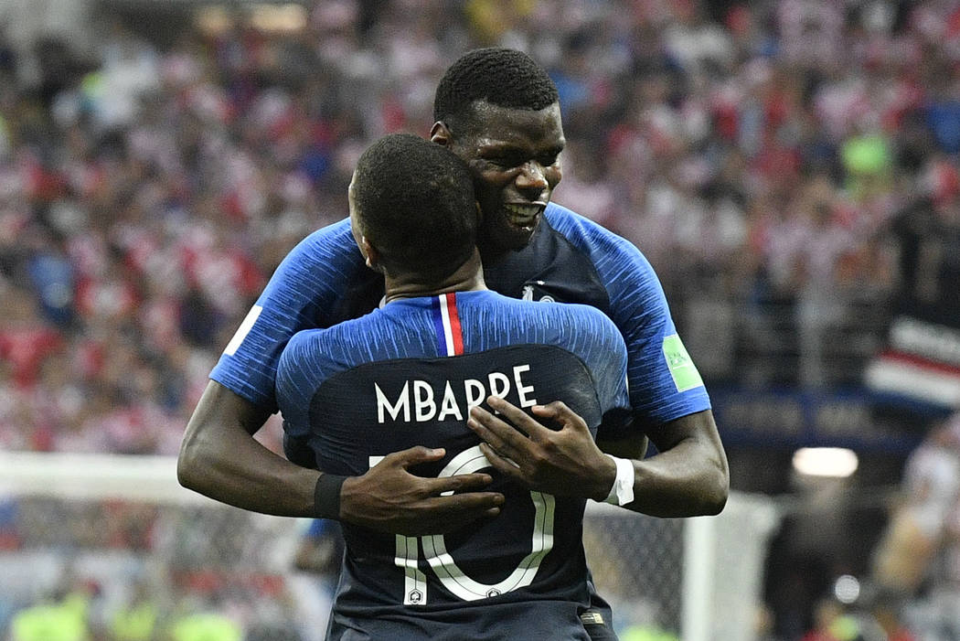 France's Kylian Mbappe, front, celebrates with Paul Pogba after scoring his side's fourth goal during the final match between France and Croatia at the 2018 soccer World Cup in the Luzhniki Stadiu ...