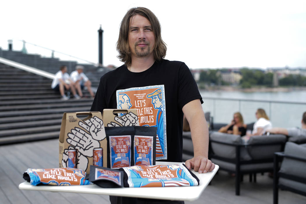 Samuli Huuhtanen, CEO of Finnish beer brewery Rock Paper Scissors poses with beer, coffee and T- shirts, labeled with cartoon caricatures depicting Russian President Vladimir Putin and U.S Preside ...