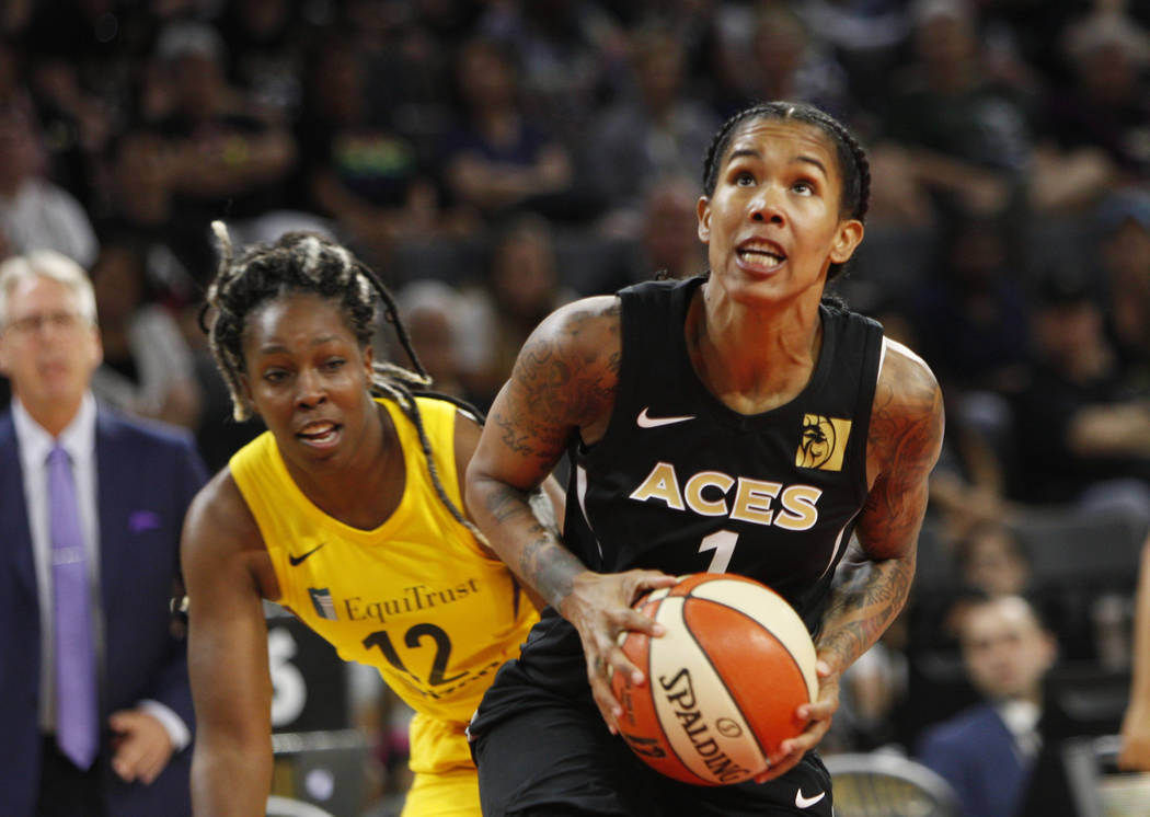 Las Vegas Aces forward Tamera Young (1) pushes past Los Angeles Sparks guard Chelsea Gray (12) to throw a basket during the first half of a WNBA basketball game at the Mandalay Bay Events Center i ...