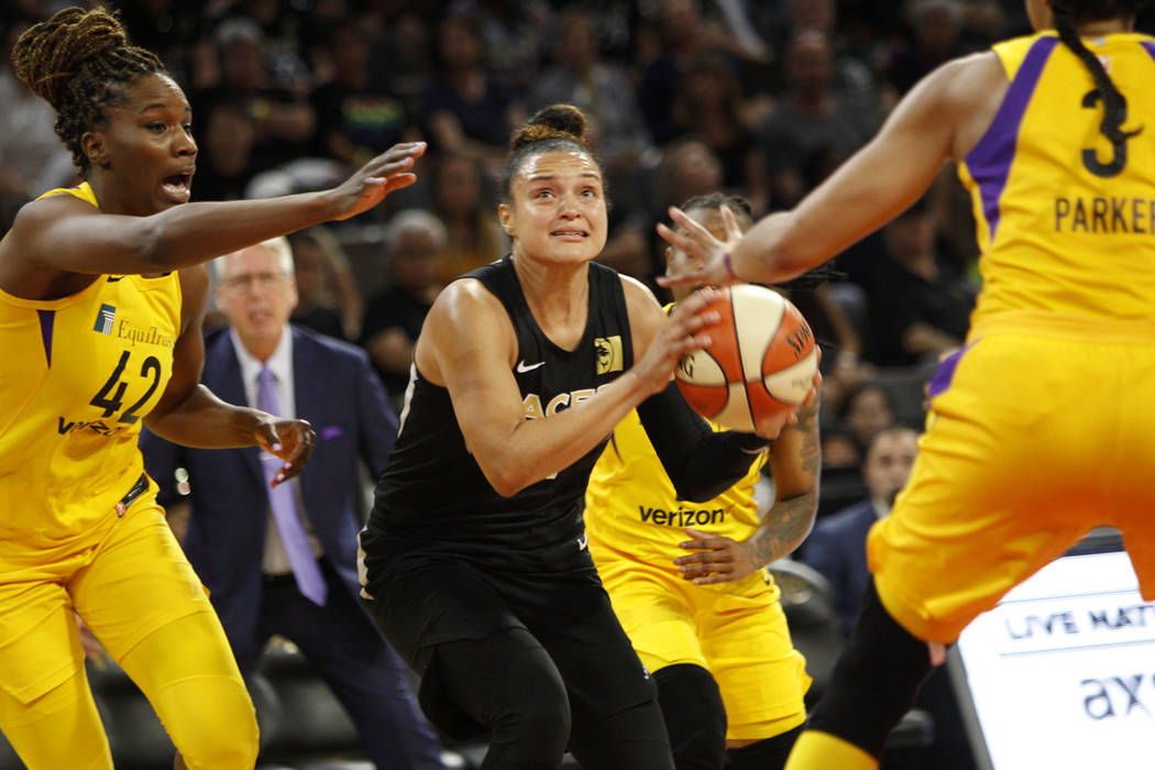 Las Vegas Aces guard Kayla McBride (21) looks to shoot a basket past Los Angeles Sparks center Jantel Lavender (42) and (3) during the second half of a WNBA basketball game at the Mandalay Bay Eve ...