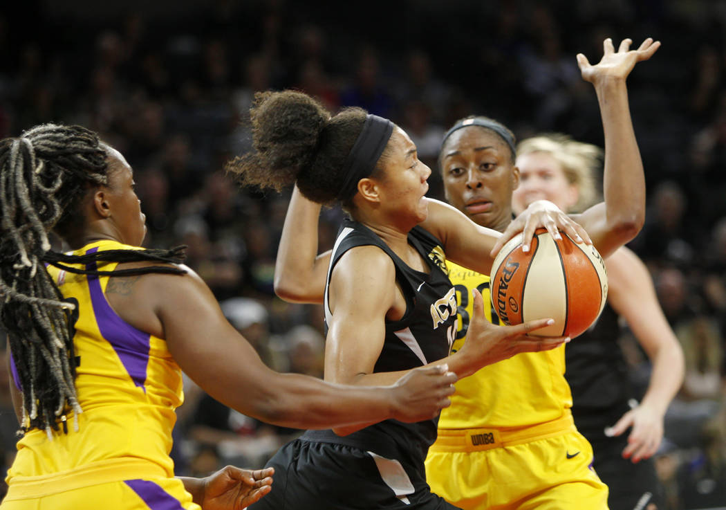 Las Vegas Aces forward Nia Coffey (12) pushes the ball through Los Angeles Sparks guard Chelsea Gray (12) and forward Nneka Ogwumike (30) during the first half of a WNBA basketball game at the Man ...
