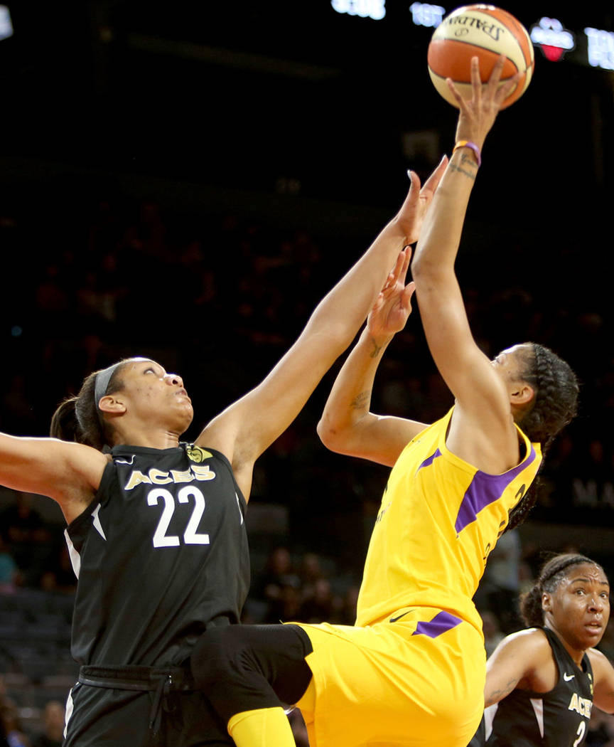 Las Vegas Aces center A'ja Wilson (22) blocks Los Angeles Sparks forward/center Candace Parker (3) during the first half of a WNBA basketball game at the Mandalay Bay Events Center in Las Vegas, S ...