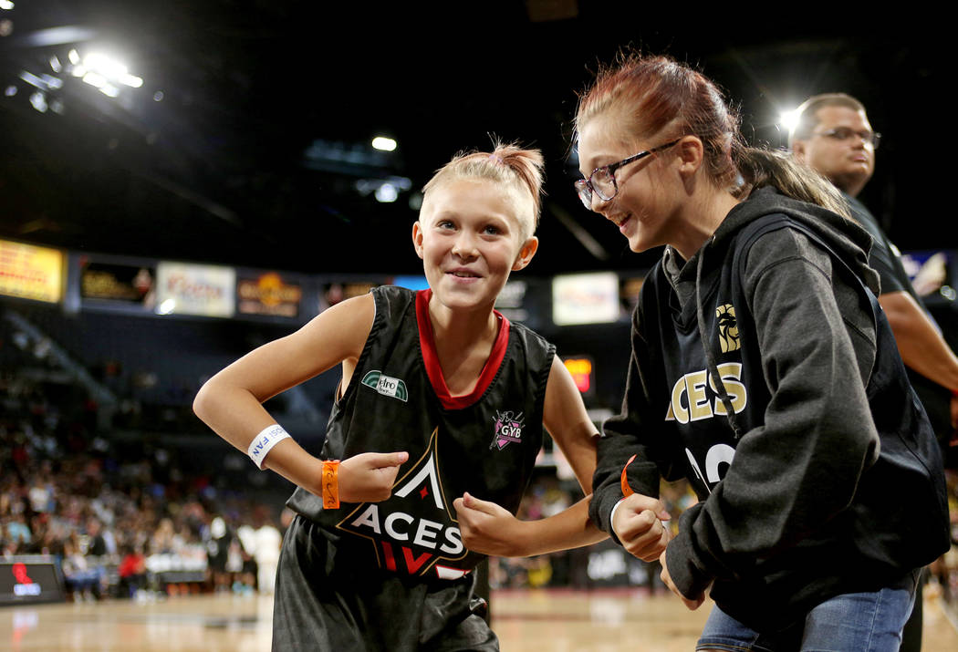 Sabbra Shirley, 9, and her sister Alani Shirley, 11, pose for the flex cam in the second half of the WNBA basketball game of the Las Vegas Aces against the Los Angeles Sparks at the Mandalay Bay E ...