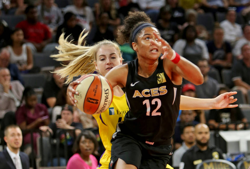 Las Vegas Aces forward Nia Coffey (12) pushes past Los Angeles Sparks guard Karlie Samuelson (44) to attempt a basket during the second half of a WNBA basketball game at the Mandalay Bay Events Ce ...