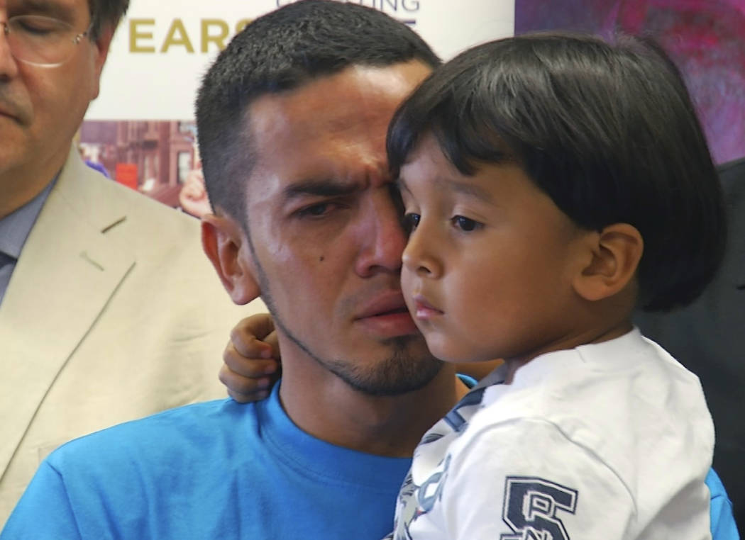 In this image taken from video, Javier Garrido Martinez holds his 4-year-old son during a news conference in New York, Wednesday, July 11, 2018. The pair were reunited after being separated for al ...