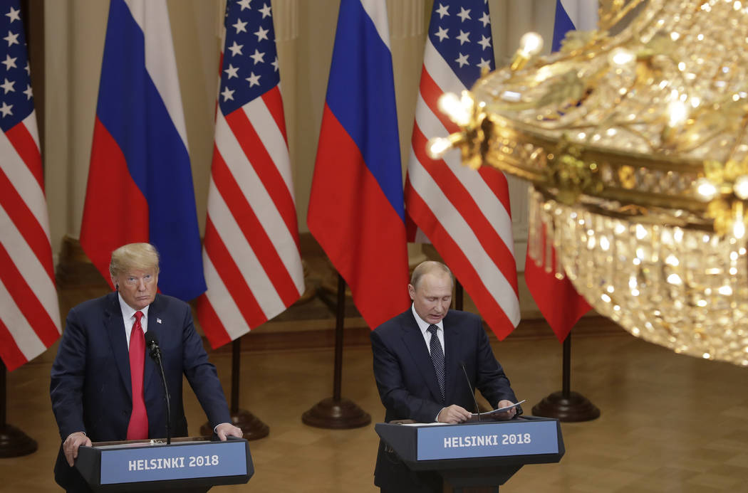 President Donald Trump, left, listens to Russian President Vladimir Putin during a press conference after their meeting at the Presidential Palace in Helsinki, Finland, Monday, July 16, 2018. (Mar ...