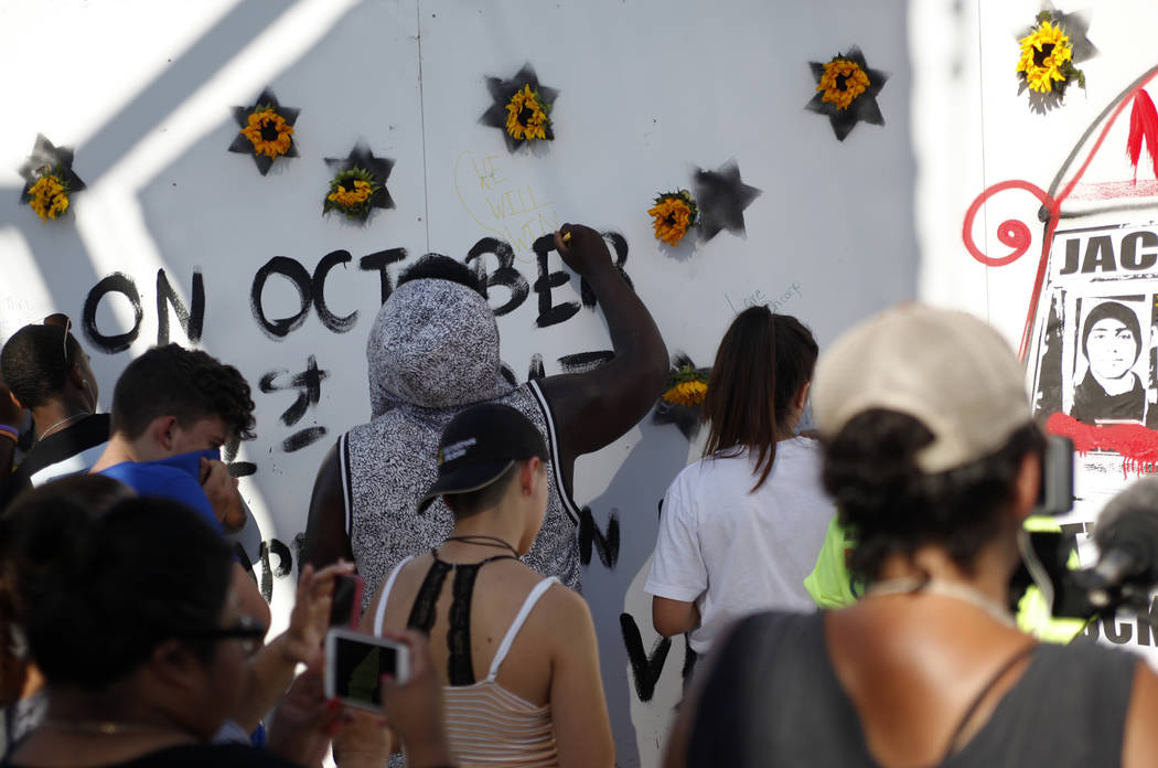 People sign a mural made by Manny Oliver at a Road to Change Voter Registration Walk at Sunset Park in Las Vegas, Monday, July 16, 2018. The event was put on by the March For Our Lives group, crea ...