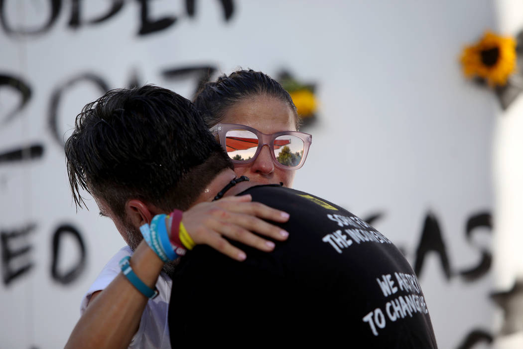 Patricia Oliver hugs her husband Manny Oliver after he painted a mural at a Road to Change Voter Registration Walk at Sunset Park in Las Vegas, Monday, July 16, 2018. The event was put on by the M ...