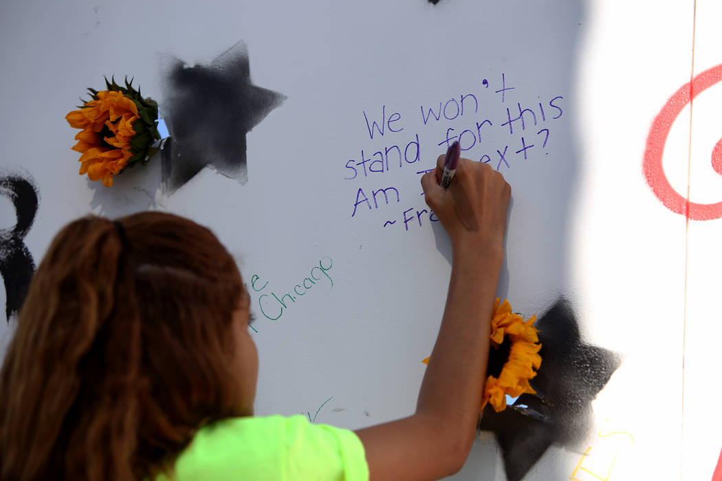 """Franlisha Vasquez, a vegas native, writes """"We won't stand for this. Am I next?"""" on a mural at a Road to Change Voter Registration Walk at Sunset Park in Las Vegas, Monday, July 16, 2018. ..."""