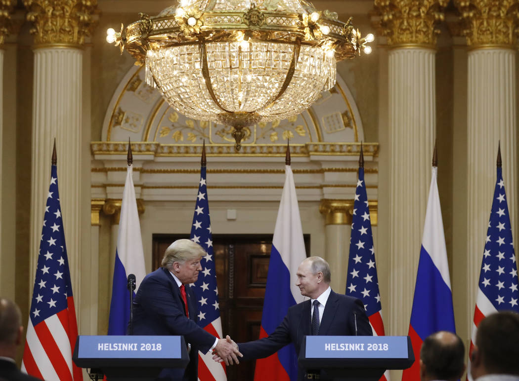 President Donald Trump, left, shakes hand with Russian President Vladimir Putin during a press conference after their meeting at the Presidential Palace in Helsinki, Finland, Monday, July 16, 2018 ...