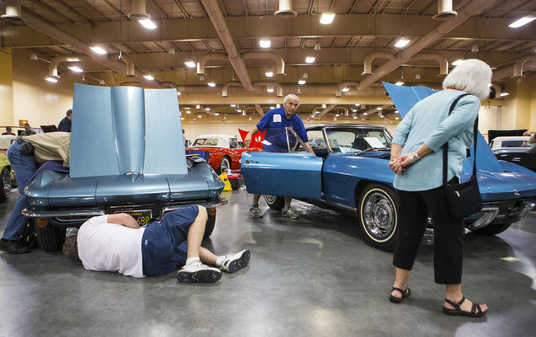 Ray Geiger, center right, checks his 1967 Corvette as a pair of attendees, left, inspect a 1967 Corvette during the National Corvette Restorers Society convention at the South Point in Las Vegas o ...