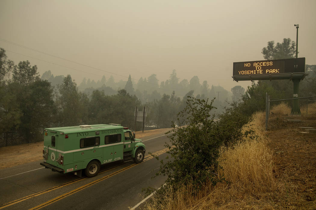 A fire transport drives along Highway 140, one of the entrances to Yosemite National Park, on Monday, July 16, 2018, in Mariposa, Calif. The road remains closed as crews battle a deadly wildfire b ...