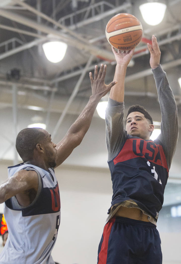 Phoenix Suns guard Devin Booker (31) shoots over Milwaukee Bucks forward Khris Middleton (54) during Team USA basketball's minicamp on Friday, July 27, 2018, at the Mendenhall Center, in Las Vegas ...