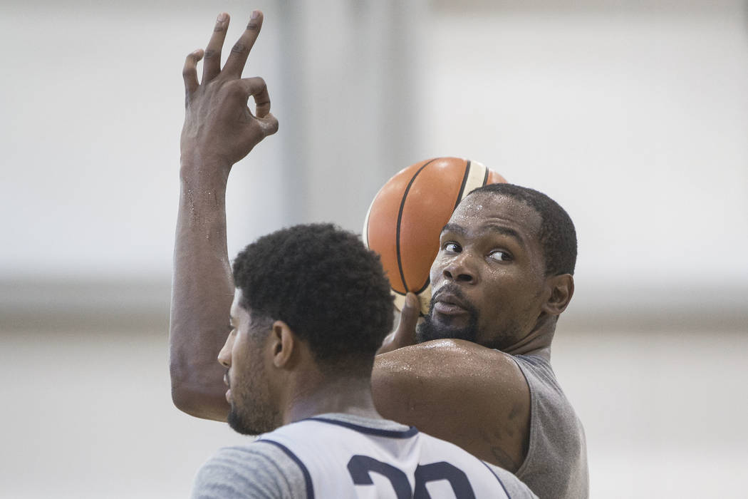 Golden State Warriors guard Kevin Durant (52) asks to confirm the score while being guarded by Oklahoma City Thunder forward Paul George (39) during Team USA basketball's minicamp on Friday, July ...