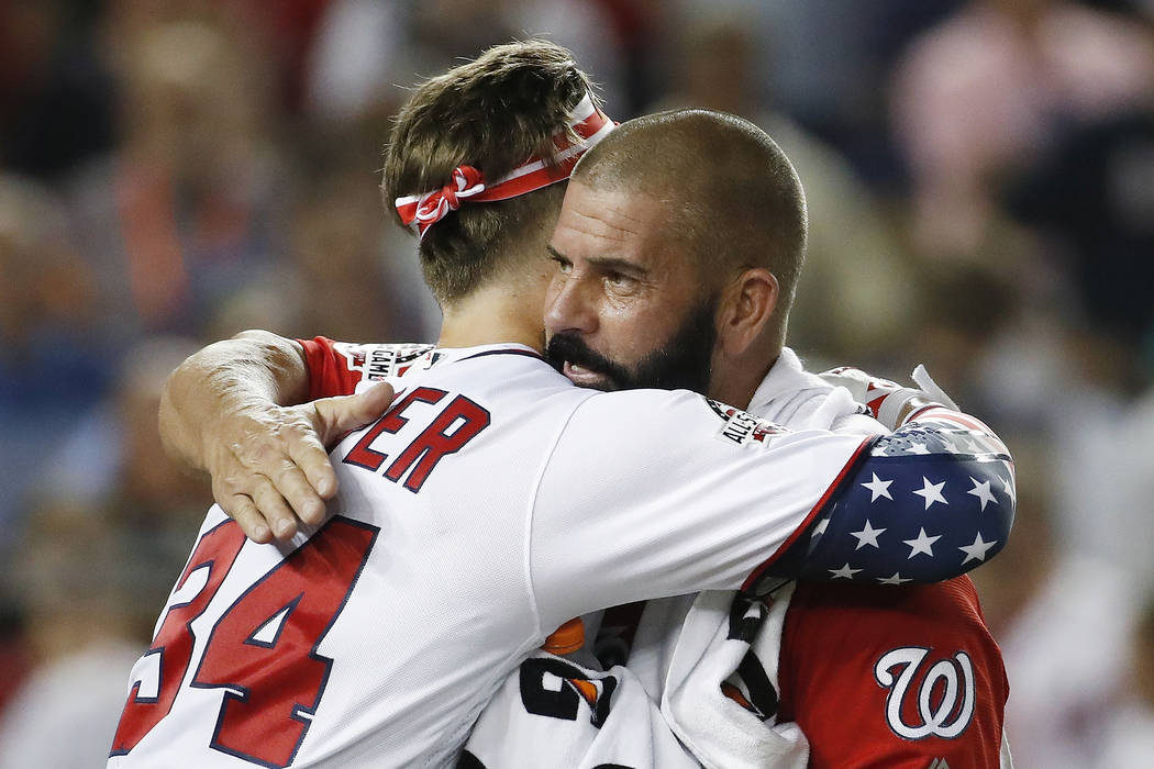 Washington Nationals Bryce Harper (34) hugs his dad Ron Harper during the MLB Home Run Derby, at Nationals Park, Monday, July 16, 2018 in Washington. The 89th MLB baseball All-Star Game will be pl ...