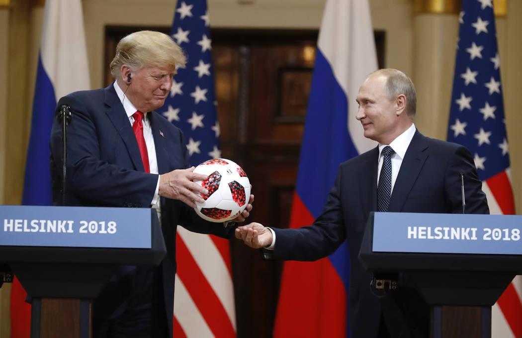 El presidente ruso, Vladimir Putin, le da un balón de fútbol al presidente Donald Trump, izquierda, durante una conferencia de prensa después de su reunión en el Palacio Presidencial en Helsin ...
