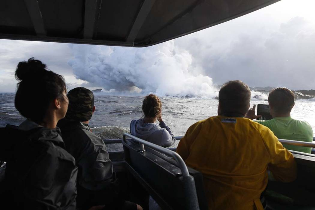 In this May 20, 2018 file photo, people watch a plume of steam as lava enters the ocean near Pahoa, Hawaii. Officials say an explosion sent lava flying through the roof of a tour boat off the Big ...