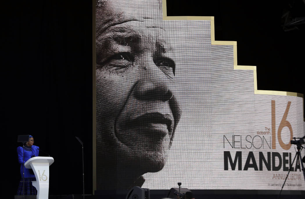 Graca Machel, left, wife of the late Nelson Mandela, background, delivers a speech at the Wanderers Stadium in Johannesburg, South Africa, Tuesday, July 17, 2018 at the 16th Annual Nelson Mandela ...