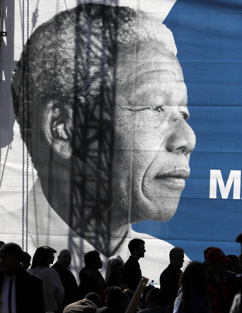 People gather below a giant banner of the late Nelson Mandela as they wait for the 16th Annual Nelson Mandela Lecture by former President Barack Obama at the Wanderers Stadium in Johannesburg, Sou ...