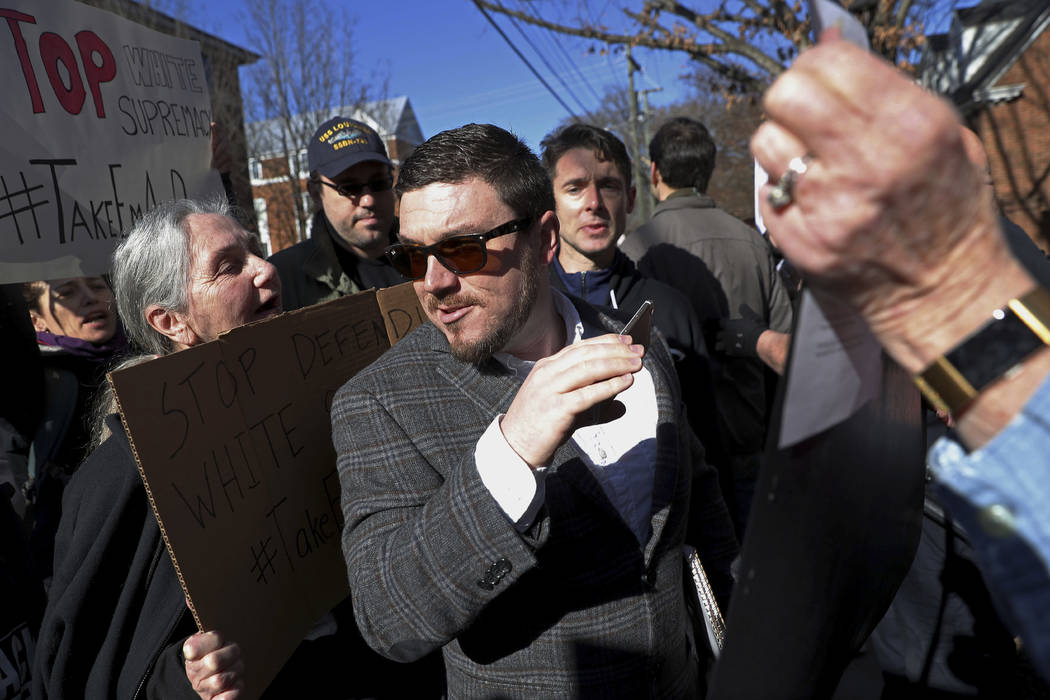 Jason Kessler walks through a crowd of protesters in front of the Charlottesville Circuit Courthouse ahead of a decision regarding the covered Confederate statues, during a rally in Charlottesvill ...
