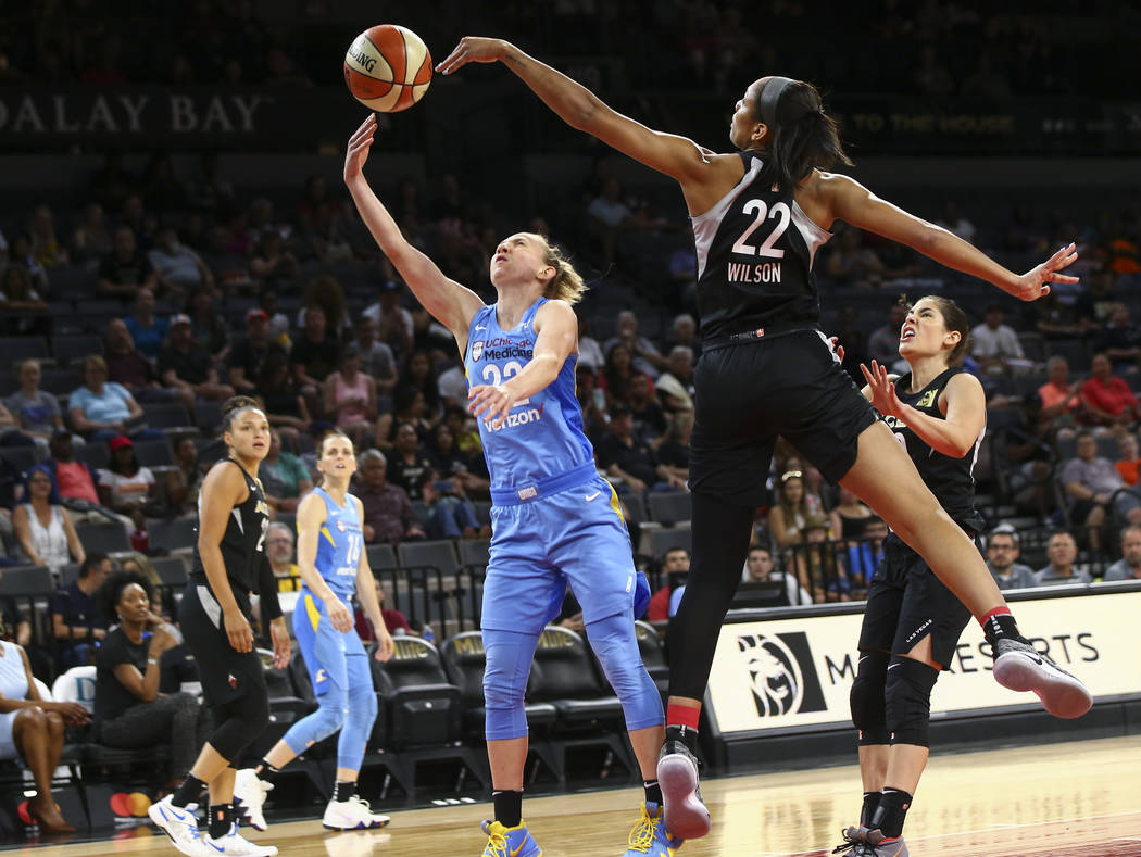 Las Vegas Aces center A'ja Wilson (22) blocks a shot rom Chicago Sky guard Courtney Vandersloot (22) during the first half of a WNBA basketball game at Mandalay Bay Events Center in Las Vegas on T ...