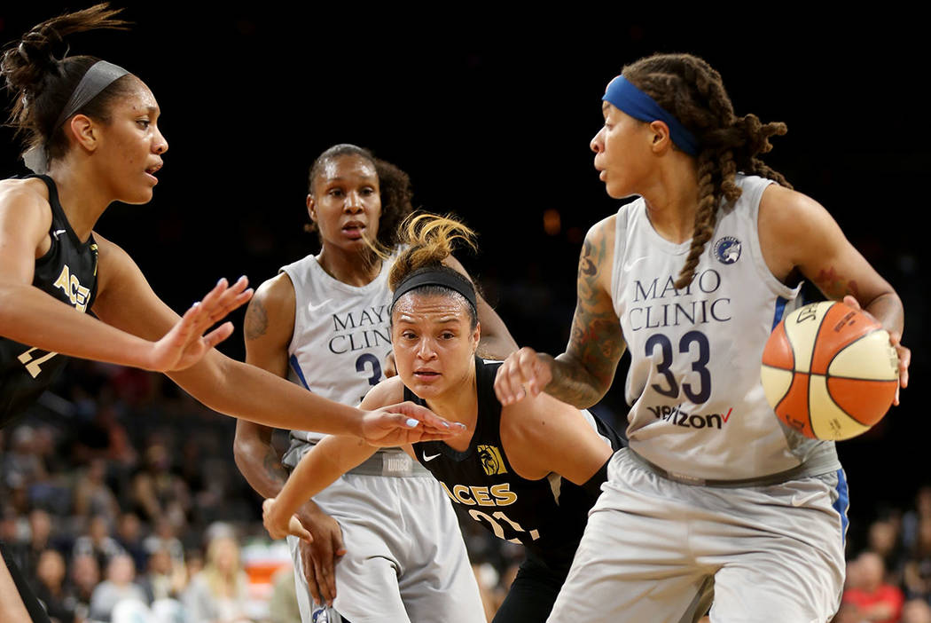 Minnesota Lynx Seimone Augustus (33) attempts to pass the ball past Las Vegas Aces A'ja Wilson (22) and Las Vegas Aces Kayla McBride (21) in the first half of a WNBA basketball game at the Mandala ...
