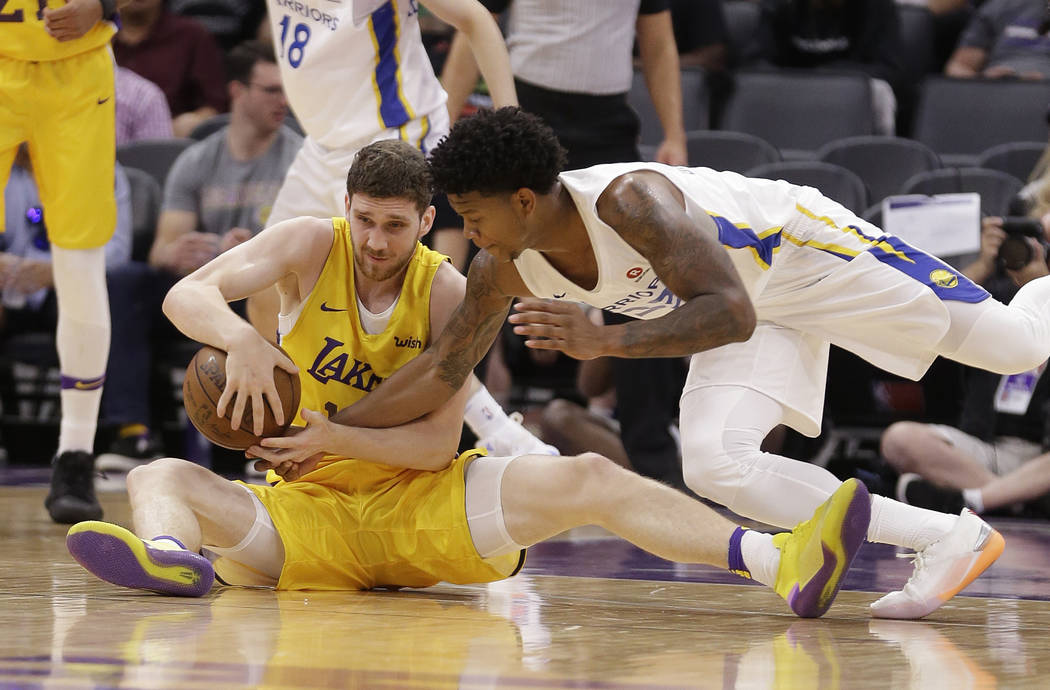 Los Angeles Lakers forward Sviatoslav Mykhailiuk, left, and Golden State Warriors guard Rion Brown battle for the ball during the first half of an NBA summer league basketball game Thursday, July ...