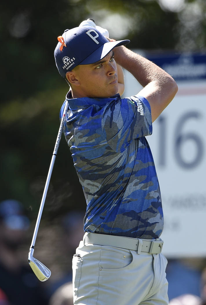 Rickie Fowler watches his tee shot on the 16th tee during the second round of the Quicken Loans National golf tournament, Friday, June 29, 2018, in Potomac, Md. (AP Photo/Nick Wass)