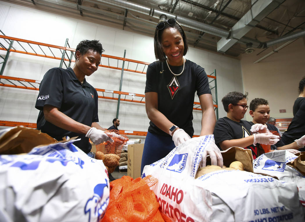 Las Vegas Aces assistant coach Vickie Johnson, left, and player A'ja Wilson package potatoes to be part of meal packages for residents in need at the Three Square food bank in Las Vegas on Tuesday ...