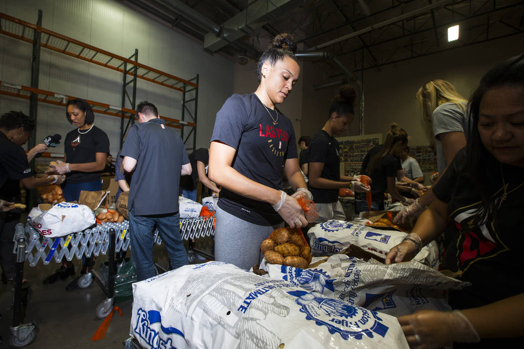 Kayla McBride of the Las Vegas Aces packages potatoes to be part of meal packages for residents in need at the Three Square food bank in Las Vegas on Tuesday, July 17, 2018. Chase Stevens Las Vega ...