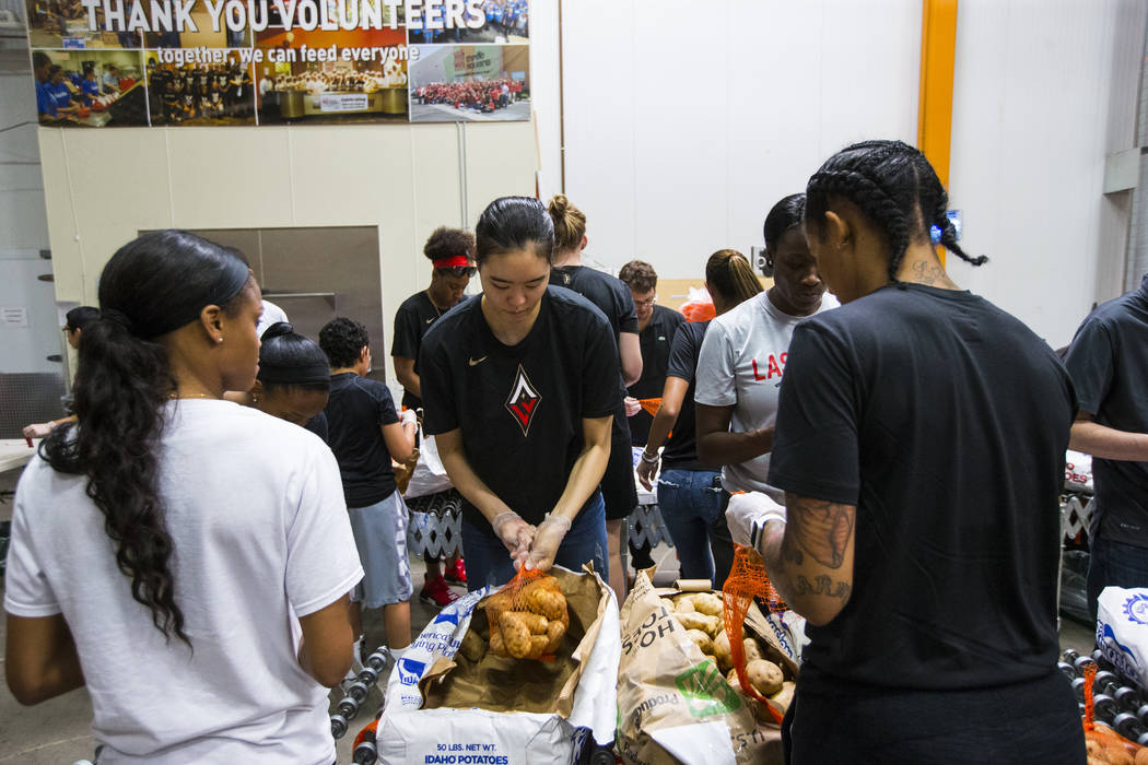 Ji-Su Park of the Las Vegas Aces, center, packages potatoes to be part of meal packages for residents in need at the Three Square food bank in Las Vegas on Tuesday, July 17, 2018. Chase Stevens La ...