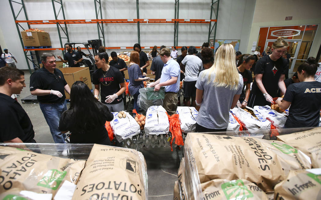 Players and staff of the Las Vegas Aces package potatoes to be part of meal packages for residents in need at the Three Square food bank in Las Vegas on Tuesday, July 17, 2018. Chase Stevens Las V ...