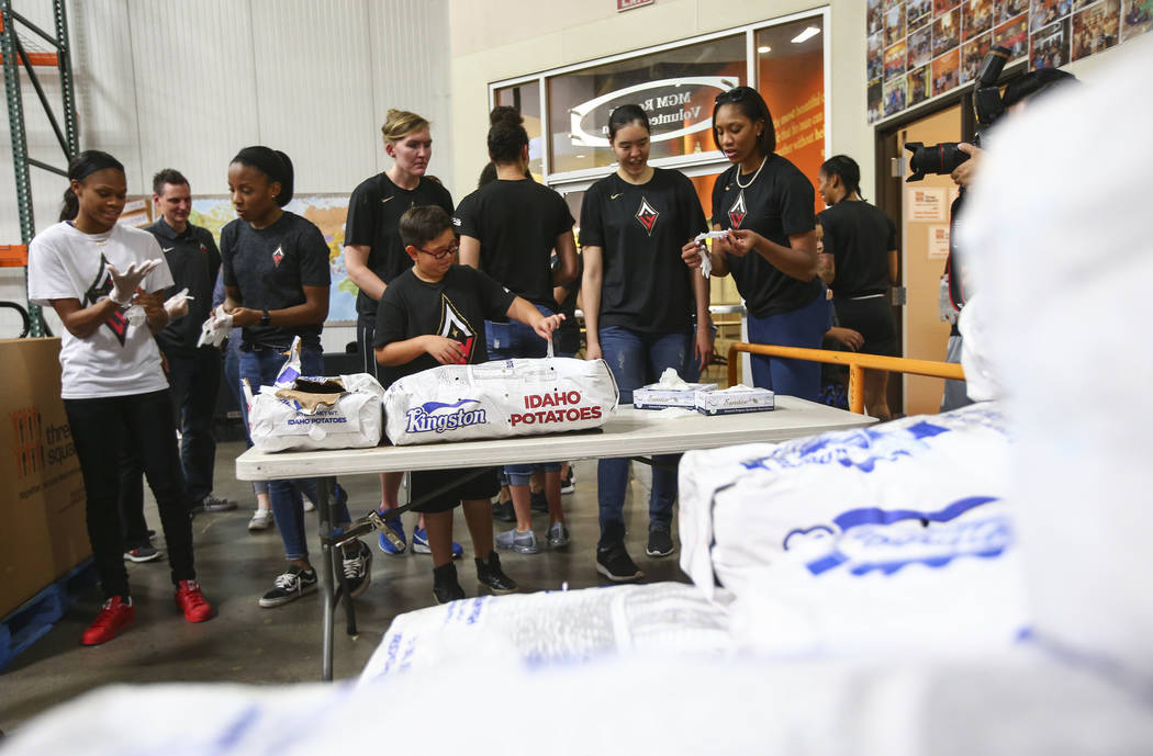 Players and staff of the Las Vegas Aces prepare to package potatoes to be part of meal packages for residents in need at the Three Square food bank in Las Vegas on Tuesday, July 17, 2018. Chase St ...