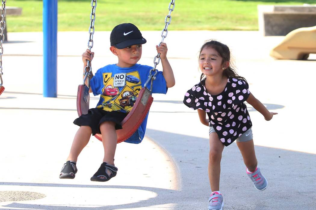 Calia Lopez, 4, pushes her brother Osiris, 2, both of Las Vegas, on a swing as they play at Sunset Park on Tuesday, July 17, 2018, in Las Vegas. Bizuayehu Tesfaye/Las Vegas Review-Journal @bizutesfaye