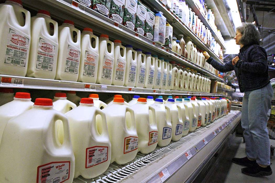 FILE - In this Feb. 11, 2009, file photo, a shopper looks over the milk aisle at the Hunger Mountain Co-op in Montpelier, Vermont. Soy and almond drinks don't come from cows, so regulators may ...