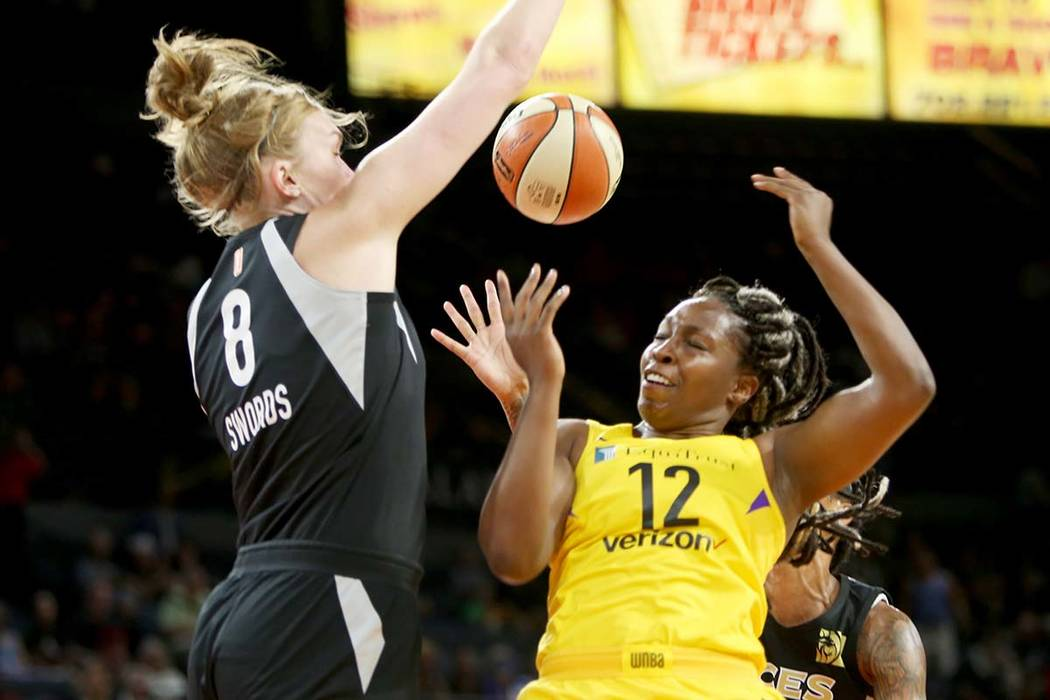 Las Vegas Aces center Carolyn Swords (8) blocks Los Angeles Sparks guard Chelsea Gray (12) during the first half of a WNBA basketball game at the Mandalay Bay Events Center in Las Vegas, Sunday, J ...