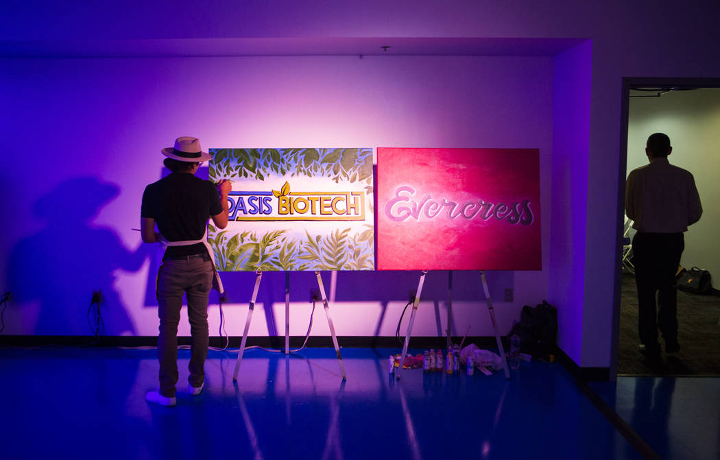 Jeremiah Kaniaupio, left, paints the Oasis Biotech logo during a grand opening event for the indoor farming company in Las Vegas on Wednesday, July 18, 2018. Chase Stevens Las Vegas Review-Journal ...