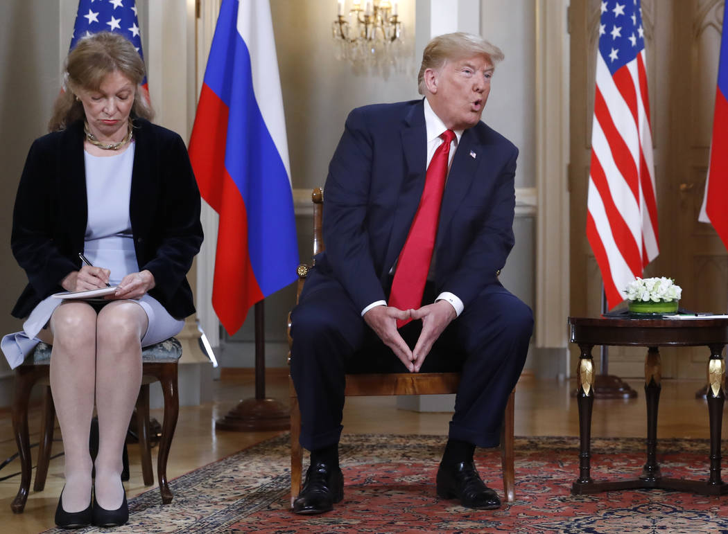 Interpreter Marina Gross, left, takes notes when President Donald Trump talks to Russian President Vladimir Putin at the beginning of their one-on-one-meeting at the Presidential Palace in Helsink ...