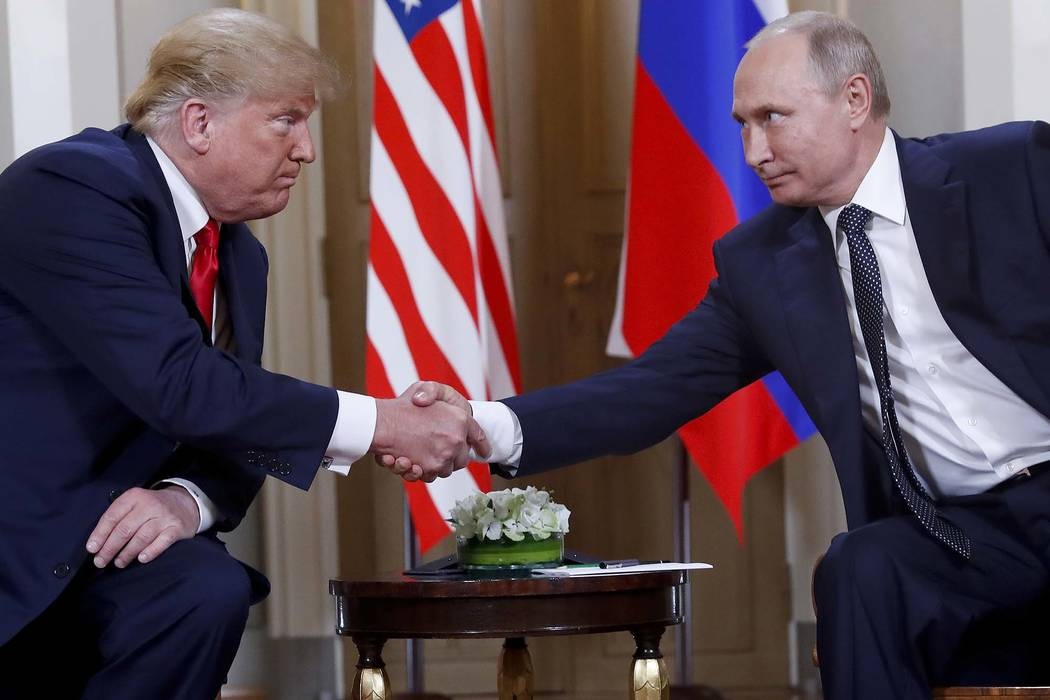 President Donald Trump, left, and Russian President Vladimir Putin shake hands at the beginning of a meeting at the Presidential Palace in Helsinki, Finland, July 16, 2018. (Pablo Martinez Monsiva ...