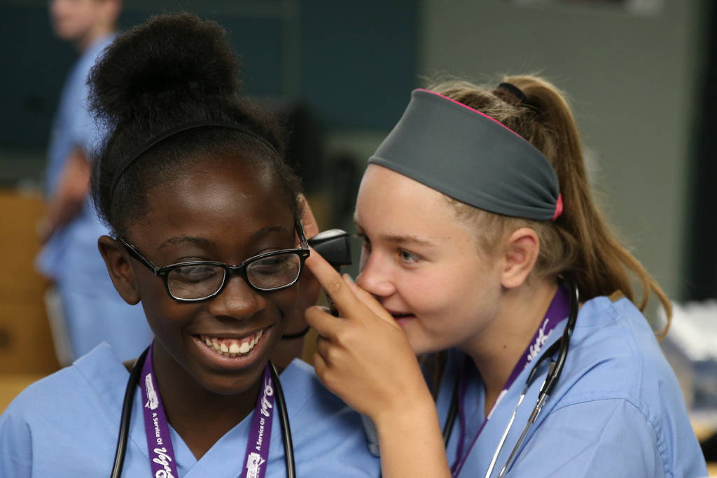 Halsey Hughes, right, 14, checks the ear of Damera Spann, 14, during CampMED at UNLV in Las Vegas, Friday, July 20, 2018. In CampMED, students interested in the medical field as a career attend la ...