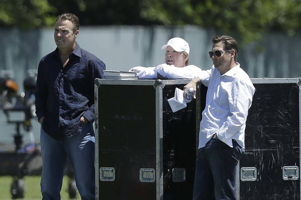 Oakland Raiders owner Mark Davis, center, watches practice with former linebacker Bill Romanowski, left, and radio broadcaster Greg Papa at NFL football minicamp in Alameda, Calif., Thursday, June ...