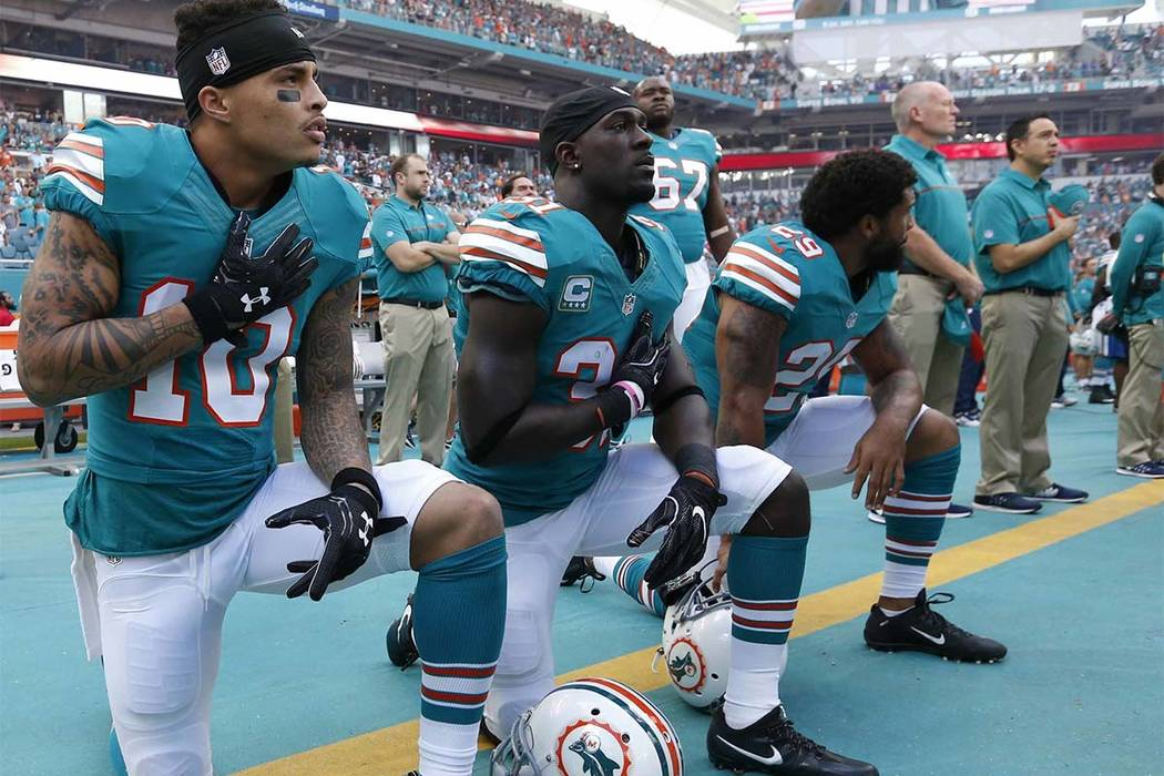 In this Sunday, Oct. 23, 2016, file photo, Miami Dolphins wide receiver Kenny Stills (10), free safety Michael Thomas (31) and defensive back Chris Culliver (29) kneel during the national anthem i ...